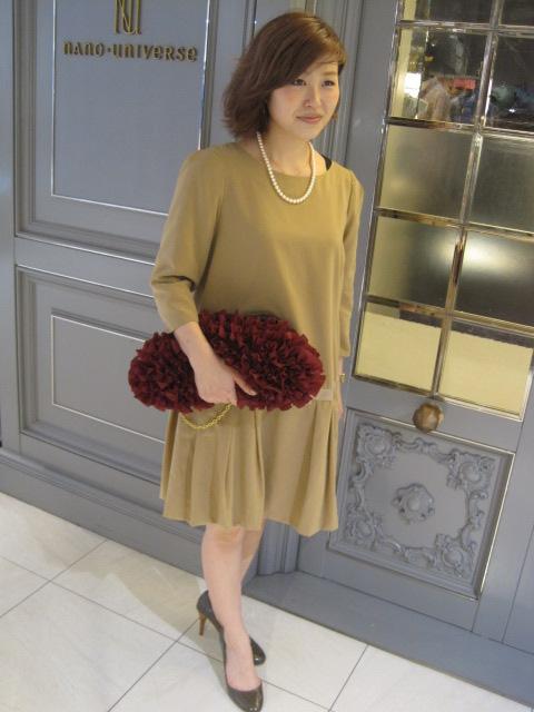 ベージュのドレスにレッドのバッグを差し色にしたコーディネート画像